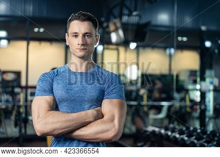 Portrait Of Active Sport Athlete Man With Six Packs Abs In Sportswear Standing With Arm Crossed Then