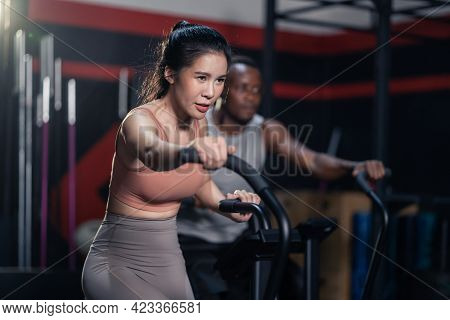 Group Of Multiethnic Fitness Trainer Workout, Sit On Stationary Bicycle In Gym Or Stadium. Athlete S