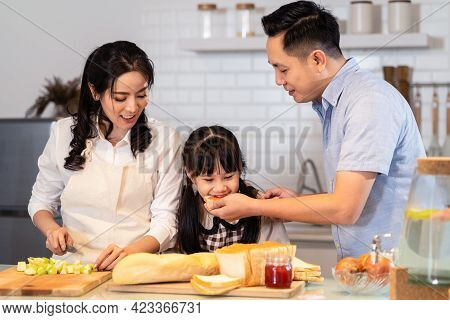 Asian Happy Family Stay At Home In Kitchen Spending Time Together Baking Bakery And Foods. Little Pr