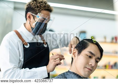 Asian Professional Male Hairstylist Combing And Use Scissors Cutting Young Man Customer\'s Hair In S