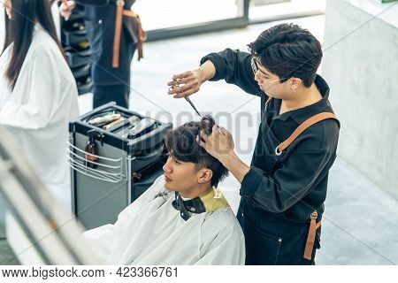 Asian Professional Male Hairstylist Combing And Using Scissors Cutting Young Customer\\\'s Hair In S