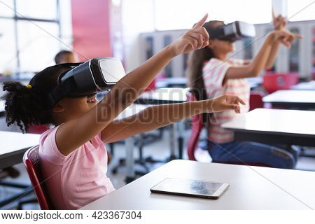 African american girl wearing vr headset gesturing while sitting on her desk in the class at school. school and education concept
