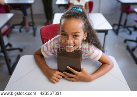 African american girl smiling while holding digital tablet sitting on her desk in class at school. school and education concept