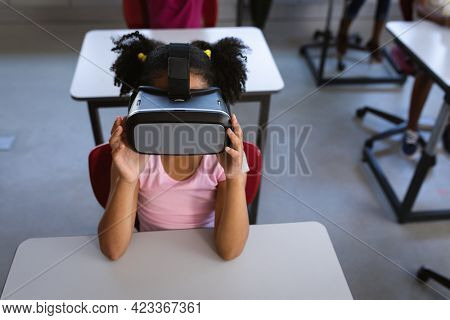 African american girl wearing vr headset while sitting on her desk in class at school. school and education concept