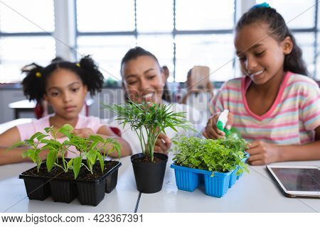 African american female teacher and two girls spraying water on plants in the class at school. school and education concept