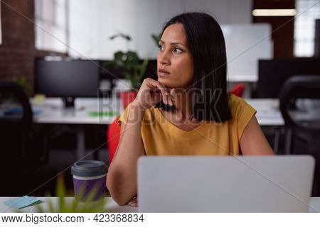 Caucasian businesswoman sitting at desk in office using laptop, looking away. working in business at a modern office.