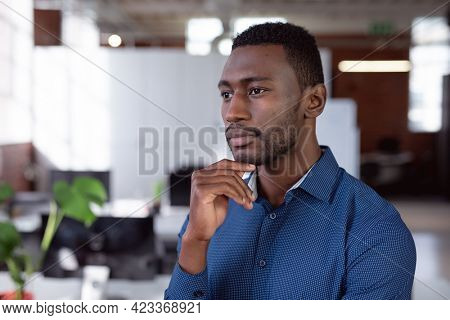 Thoughtful african american businessman standing in office looking away. working in business at a modern office.