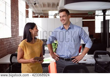 Happy caucasian male and female colleague talking at desk smiling, woman holding tablet. working in business at a modern office.