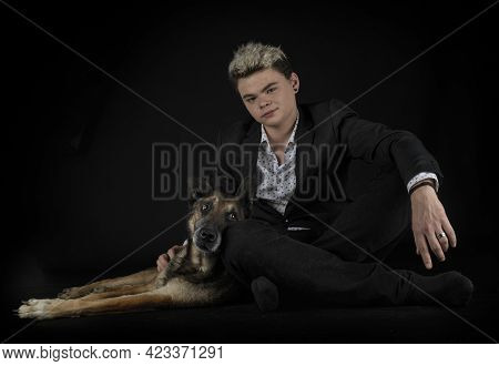 Belgian Shepherd And Young Man In Front Of Black Background