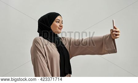 Happy Young Arabic Woman In Hijab Taking Selfie While Posing Sideways With Smartphone On Light Backg