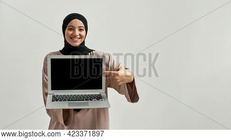 Happy Young Arabian Woman In Hijab Demonstrating Black Laptop Screen While Posing On Light Backgroun