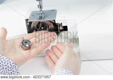 Female Hands Hold A Bobbin Case On The Background Of A Sewing Machine.