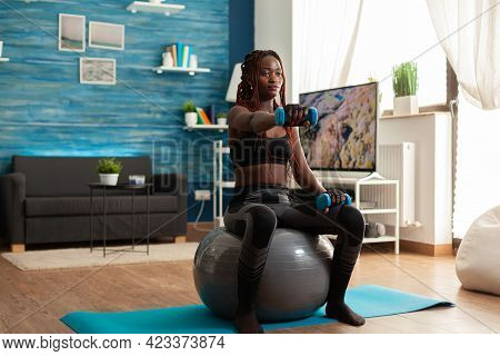 African Woman Using Stability Ball Keeping Outstretched Arms Working Out Shoulders Using Blue Dumbbe
