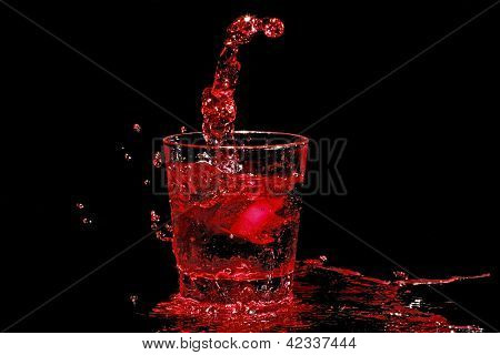 Ice cube splashing into a glass of red wine
