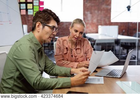 Diverse male and female colleague sitting at table with laptop and paperwork discussing. working in business at a modern office.