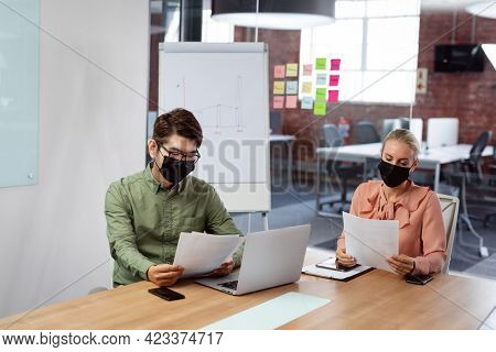 Diverse male and female colleague in face masks sitting at table with laptop reading paperwork. working in business at a modern office during coronavirus covid 19 pandemic.