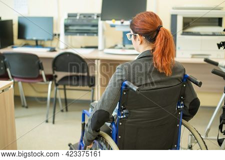 Young Caucasian Woman In A Wheelchair In A University Auditorium. Inclusive Faculty.