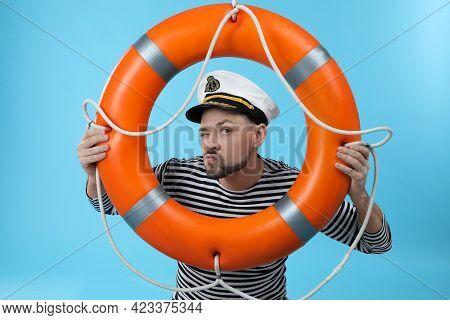 Funny Sailor With Orange Ring Buoy On Light Blue Background