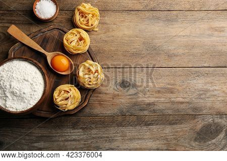 Uncooked Homemade Pasta And Ingredients On Wooden Table, Flat Lay. Space For Text