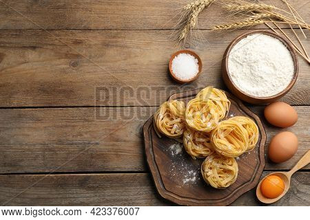 Flat Lay Composition With Uncooked Homemade Pasta And Ingredients On Wooden Table. Space For Text