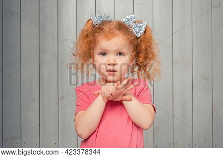 Cute Timid Redhead Little Girl 4-6 Years Old In Casual Pink T Shirt Standing Shy And Silly, Looking