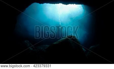 Beautiful And Fantasy Underwater Photo Of A Scuba Diver Inside A Cave In Rays Of Sunlight. From A Sc