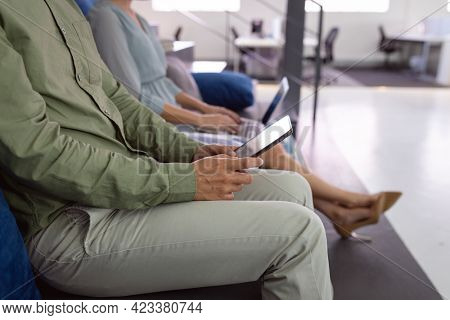 Midsection of male and female colleague sitting in office foyer using tablet and laptop. working in business at a modern office.