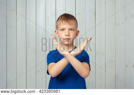 Serious Preteen Boy In Blue T Shirt Holding Two Arms Crossed, Say No, Stop Gesture, Warning Of End F