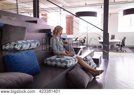 Happy caucasian businesswoman sitting in office foyer using laptop. working in business at a modern office.