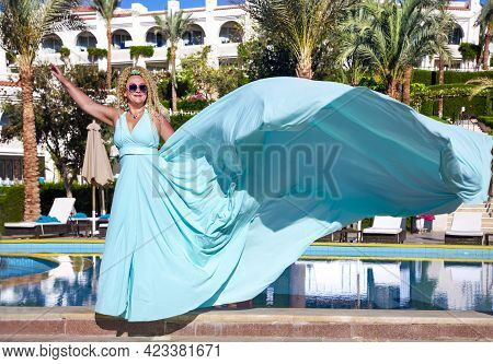 A Beautiful Slender Woman With Curly Hair In A Fluttering Blue Long Evening Luxurious Dress Stands N