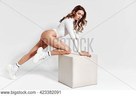 Sexy Sporty Woman In White Bodysuit Posing On White Studio Background