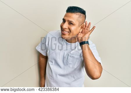 Young latin man wearing casual white t shirt smiling with hand over ear listening an hearing to rumor or gossip. deafness concept.