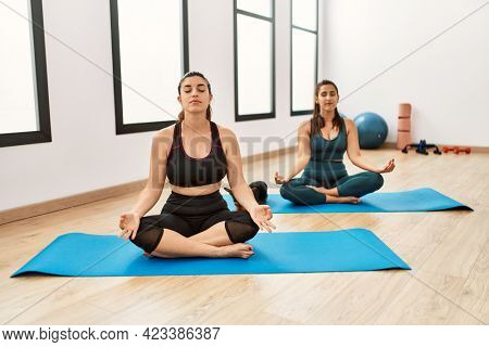 Two hispanic women friends training at the gym sitting on yoga mat with dog relax and smiling with eyes closed doing meditation gesture with fingers. yoga concept.