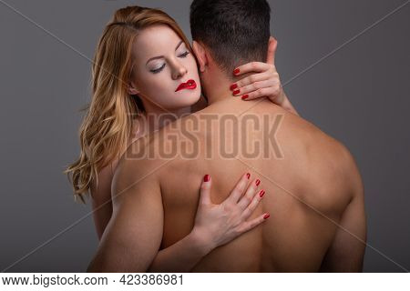 Passionate Blonde 20s Caucasian Woman Embracing Man While Biting Red Lips, Shirtless Upper Body