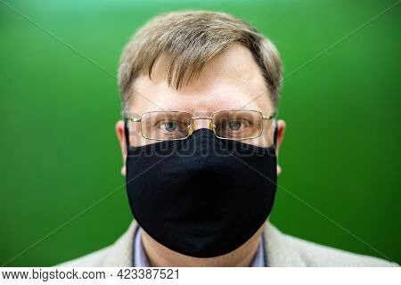 A Strict Teacher In A Protective Mask And Glasses At The Green Board In The School.