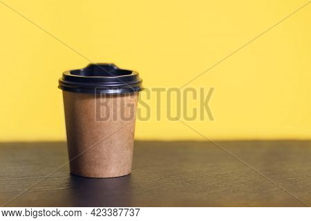 Disposable Coffee Cup For Cafe On A Bar Table. Brown Cardboard Mockup Of Eco Friendly Coffee Cup Wit