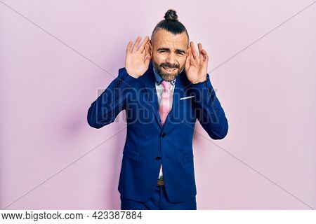 Young hispanic man wearing business suit and tie trying to hear both hands on ear gesture, curious for gossip. hearing problem, deaf
