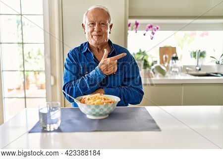 Senior man with grey hair eating pasta spaghetti at home cheerful with a smile of face pointing with hand and finger up to the side with happy and natural expression on face