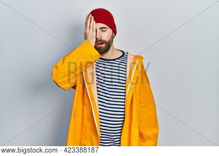 Caucasian man with beard wearing yellow raincoat yawning tired covering half face, eye and mouth with hand. face hurts in pain.
