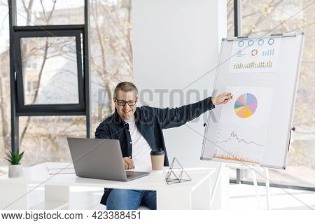 A Man Dressed In Casual Clothes Works In The Office, Sits At A Table Near A Laptop And Holds An Onli