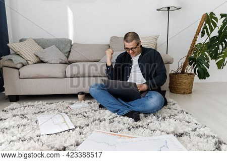 A Man Dressed In Casual Clothes Works At Home, Sits By The Sofa And Works With A Laptop.