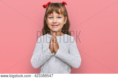 Little caucasian girl kid wearing casual clothes praying with hands together asking for forgiveness smiling confident.