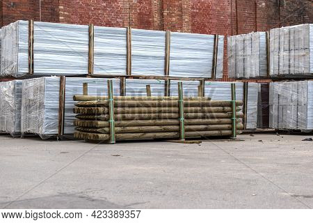 Material For Protective Wall Stacked In The Yard. Heaps Of Wooden Fence Posts, White Protective Fenc