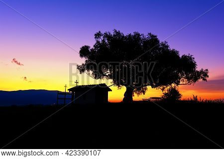 Silhouette Of The Christian Chapel Near The Village Of Plana, Bulgaria And A Tree With A Large Crown