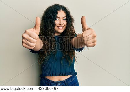 Young brunette woman with curly hair wearing casual clothes approving doing positive gesture with hand, thumbs up smiling and happy for success. winner gesture.