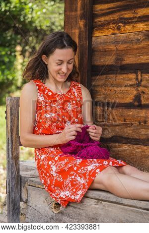 Woman Knits Sitting On The Veranda Of A Wooden House, Needlework, The Smiling Girl Knits From Pink Y