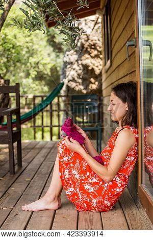 Woman Knits On The Veranda Of The House. Girl Knits A Hat. Doing Needlework At Home In Your Free Tim