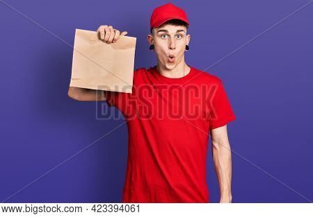 Young caucasian boy with ears dilation holding take away paper bag scared and amazed with open mouth for surprise, disbelief face