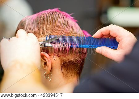 Young Caucasian Woman With Pink Hair Getting A Short Haircut By A Male Hairdressers Hands In A Haird
