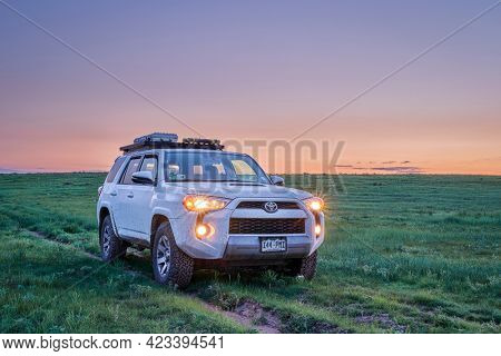Keota CO, USA - June 8, 2021: Toyota 4Runner SUV (2016 Trail edition) before sunrise in Pawnee National Grassland in northern Colorado, late spring scenery with green grass and wildflowers.